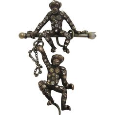 I love this quirky brooch....it's guaranteed to make you smile! One monkey sits complacently on the bar pin while the second monkey dangles beneath