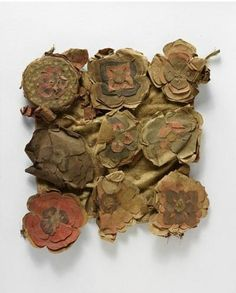 7th-10th C. 9 Paper Flowers of colored paper resting on a square of fabric. Recovered from Cave 17 of the Mogao Grottoes. This shrine site is one of China's great Buddhist pilgrimage complexes and is situated near the oasis town of Dunhuang