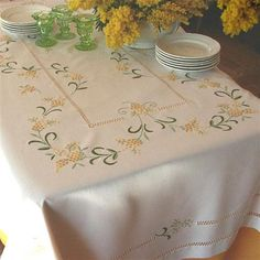 Mimosa, first flower of spring, blossoms on this hand-embroidered tablecloth. This yellow flower, hand-embroidered in flat-stitch and stem-stitch and First Flowers Of Spring, Kitchen Tablecloths, Cross Stitch Rose, Crochet Bracelet, Hand Embroidery Patterns, Cotton Bedding, Pansies, Needlepoint, Delicate