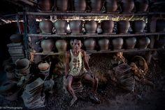 A man sit next to pots at Pot factory in Tontay , Myanmar.