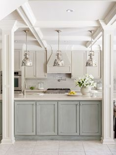 Chrome pendant lights, pale blue cabinets, coffered ceiling, subway tile, coastal design...