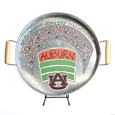 Serve your friends, family and fellow Tiger fans in style with our Metal Auburn Tray! This galvanized metal tray features two wooden handles for easy carrying, and an overhead view of Jordan-Hare Stadium. Whether you're serving drinks or using it as a kitchen catch all, it's sure to be a favorite! Measures 17 x 14.