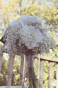Simple, all white rustic bouquet made of real baby's breath and artificial white dahlias & roses. Complete with rustic burlap and lace wrap.