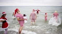Santa Clauses swim in the ocean at the 2015 World Santa Claus Congress near…