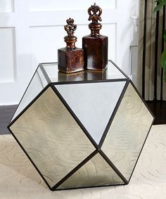 Matty Polygon Table Reflect the glory of a prized rug or counteract staid architecture when you include the Matty Polygon Table in your room's design. A truly unconventional choice for a night table, this surface comes into its own when its mirrored facets fracture the image of a forceful yet balanced living-room look. Black edges highlighted with red rust add a note of age to this practical sculpture.
