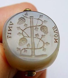 antique Georgian (circa 1780) grey agate swivel seal which has three sides each one carved with an intaglio. Two of the intaglios are classical male heads and the third one appears to be grape vines entwined around a staff with the words NOUS UNIT (unites us). The decorative mount is gilt metal.  It measures approx 1.7/8 inches (47mm) in height including the mount. Each face of the agate measures approx 1 inch (25mm) in diameter with slight variations to each one.