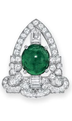 *AN ART DECO EMERALD AND DIAMOND CLIP BROOCH, BY TIFFANY & CO. Set with an oval cabochon emerald, within a circular and baguette-cut diamond geometric frame, mounted in platinum, circa 1925 Signed Tiffany & Co.