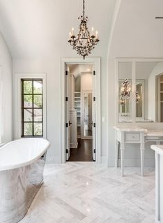 Feel at home in this gorgeous white and gray French style bathroom boasting an iron and crystal chandelier hung from an arched ceiling over marble herringbone floor tiles between a cast iron tub facing an uncovered window and a light gray French make up vanity topped with a white marble countertop fixed beneath inset vanity mirrors framed by light gray walls lit by French crystal sconces.