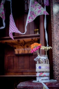 my DIY vintage wedding decor. decorated jam jars! bunting, ikea flowers, ribbons & buttons