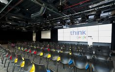 An area called the Town Hall allows seating for 200 people and features velvet curtains, exposed ceilings and a video wall. Google Headquarters, Office Training, Google Office, Exposed Ceilings, Lecture Theatre, Office Themes, Office Floor, New London, Video Wall