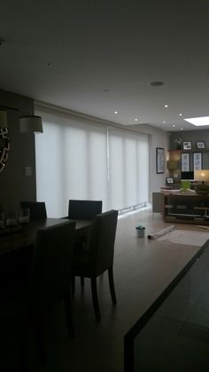 Huge electric blinds to cover these bifold doors in the heart of London, with motorised control, Mermet Screen fabrics and powder coated pelmets by Deans Blinds And Awnings