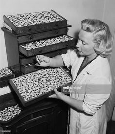 Mollie Surman of Kingston in Surrey with her stock of glass eyes, 18th July 1957. Mrs Surman makes the eyes herself, a craft passed down to her by her father, Mr G. Taylor and her grandfather.