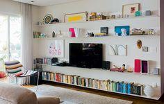 Organize as prateleiras. Livros e objetos que você já tem podem virar decoração na disposição certa. Uma boa ideia é arrumar os livros por cores. Projeto do arquiteto Gustavo Calazans