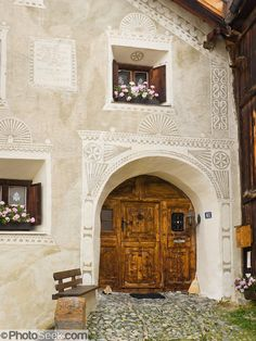 """Cobblestones lead to front door of an historic building decorated with sgraffito (or scraffito, plural: sgraffiti), a technique of wall decor where layers of plaster tinted in contrasting colors are applied to a moistened surface. 17th century Guarda is one of the best preserved and characteristic villages of the Lower Engadine. Visit Guarda in Graubünden canton, Switzerland, the Alps, Europe. The Swiss valley of Engadine translates as the """"garden of the En (or Inn) River"""" (Engadin in ..."""