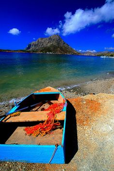 Small wooden boat with net on the beach with view of Telendos Island, Kalymnos Island, Dodecanese, Greece