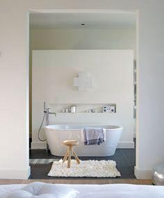 Mooi vrijstaand bad en wand waar douche en toilet achter zijn verborgen.