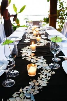 Instead of the flower boxes and fake flowers I love the idea of this sea glass on the tables!!!