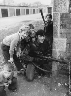 1981: Schoolboys in a Catholic area of Belfast at play on the streets near a British soldier on patrol