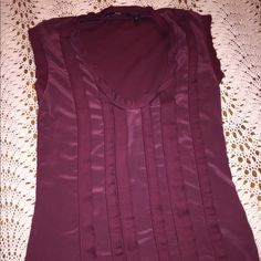 Bargain! Hugo Boss dressy sleeveless tee This is a burgundy sleeveless tee. There is a cool ribbon detail on the front. The shirt is 14 inches wide. From the neck to the bottom of the shirt is 23 inches long. The neck hole is 9 inches. Good used condition. No size is marked but it looks like a large. Hugo Boss Tops Camisoles