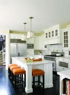 Dark dark floors, white cabinets and pop of color with green and orange accents.