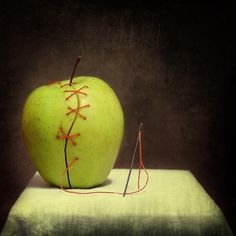An apple which has been split has been put back together with sewing. Gives off an abstract effect.