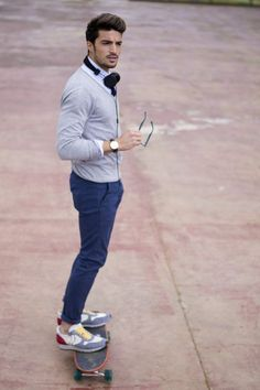 Shop this look on Lookastic:  https://lookastic.com/men/looks/cardigan-dress-shirt-chinos-athletic-shoes-watch/12239  — White Dress Shirt  — Grey Cardigan  — Dark Brown Leather Watch  — Blue Chinos  — Multi colored Athletic Shoes
