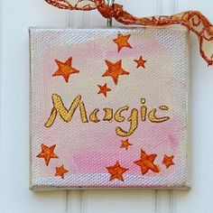 This hand painted ornament on a mini canvas will be a beautiful addition to your holiday and Christmas tree decoration. With just one word - magic - it describes this special season and time of the year. The minimalist art of just a few stars and the faint pink color underscore the magic of the season. The ornament is painted with acrylic and metallic paints. A screw-eye is attached to the top of the canvas for easy hanging. A copper organza ribbon with swirls decorates the top and a narrow…