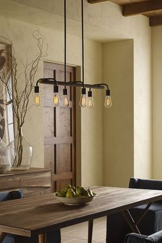 Now trending: Edison bulbs and industrial lighting styles. A linear chandelier with vintage, industrial elements makes for a key focal point above a farmhouse table.