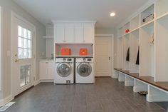 Lovely laundry room and mudroom combo features an enclosed washer and dryer under shelf and closed cabinets beside a laundry room sink atop gray staggered tiled floor.