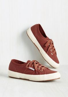 Take your warm attitude on the go by lacing into these rust red tennis shoes and amiably ambling about your day. Bronze grommets, comfy footbeds, and low platforms made of ivory rubber all maintain a friendship on these canvas kicks by Superga, making for a smile-inspiring pair that you'll love to wear!