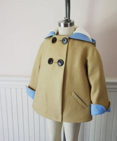 Our precious Luxe Little Rabbit jacket is perfect for little rabbits ready to hop into action! Handmade of camel colored 100% wool felt, the clean, classic style features cuffed sleeves which roll down for longer wear, and a super cozy lining. Welt pockets lined in blue will warm a chilled little paw. Styled with a shorter length to facilitate active bunny races, possibly the cutest thing ever with jeans and a tee!  Sleeves lined in poly peau de soie to slide easily on and off over clothing…