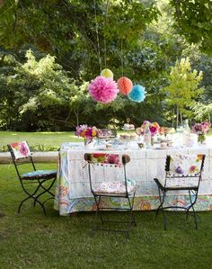 Give your garden party a fun festival vibe with colorful pom-poms and bright floral fabrics!