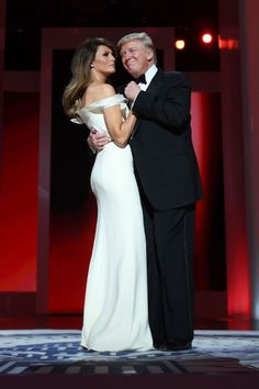 Melania Trump has opted for a white, off-the-shoulder gown by Hervé Pierre (not by Carolina Herrera, as previously reported) for the Inaugural Ball. The new First Lady revealed the tailored look—featuring a thin red cord at the waist, subtle ruffle detail and thigh-high slit—while arriving at the Freedom Ball with her husband President Donald Trump after a long day of inaugural activities, just before taking off on their first dance.