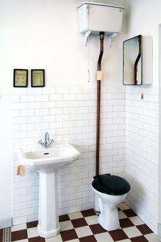 Högspolande wc med vita konsoler och kopparrör. Svart bakelitsits och spolhandtag av porslin ingår. S-lås. Spolar 6 liter.