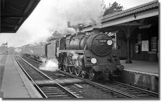A BR 4-6-0 hurries through New Milton with an up relief for London. Hampshire, England.