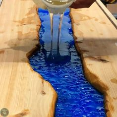 Learn how to make a DIY live edge river table with epoxy and embedded rocks.