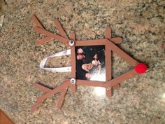 Easy christmas craft!  I helped my 4 year old make this.  All we needed was: 10 Popsicle sticks Brown paint White craft glue A little ribbon Googly eyes A red Pom And a photo Cute & easy gift for Grandma!