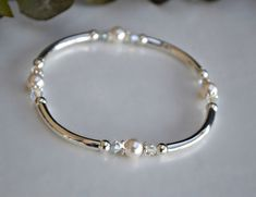 Set of 3 stretchable silver bangles made with 6mm Swarovski crystal pearls, 4mm Swarovski crystals and silver bars. Fits wrist sizes 6-71/2