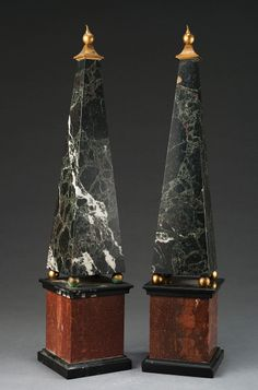 Pair of Green Marble Obelisks with decorative ormolu bronze detail at the top of each Obelisk ; both are supported by 4 gilded metal balls ; with typical square base of red marble contrast ; on black marble plinth (h 53 cm)