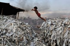 A child jumps on the waste products used to make poultry feed as she plays in a tannery at Hazaribagh in Dhaka, Bangladesh. Luxury leather goods sold across the world are produced in a slum area of Bangladesh's capital where workers, including children, are exposed to hazardous chemicals and often injured in horrific accidents. None of the tanneries packed into the Hazaribagh neighborhood treat their waste water, which contains animal flesh, sulphuric acid, chromium and lead, leaving…