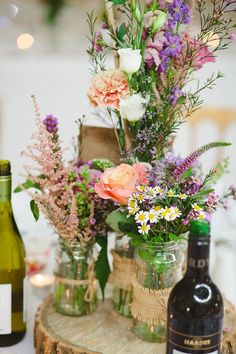Pretty rustic table centre pieces using roses and wild flowers, recycled jam jars and hessian.