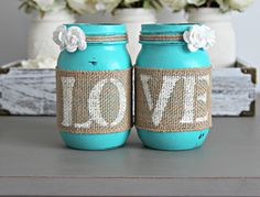 Two decorative Mason Jars in Turquoise . Each jar is hand painted & distressed, decorated with natural burlap with old white letters spelling LOVE. and two paper, off white roses. SIZE: REGULAR MOUTH                                                                                                                                                                                  More