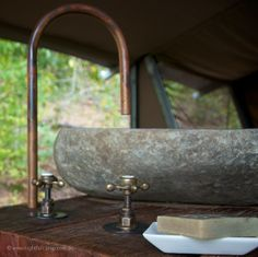 Hand-formed copper spouts, aged brass tapware, hand-carved stone basins @Kate Titsworth Edwards camp wilderness luxury tent # glamping experience