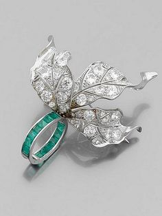 Paul Flato 1940 Rare Pin It has three leaves  richly paved with brilliant-cut diamonds  retained by a ring of calibre-cut emeralds  Platinum setting. Dimensions: 6.7 x 5.5 cm Circa 1940.