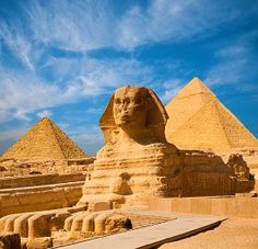 pic of great pyramids - Egyptian Great Sphinx full body portrait with head feet with all pyramids of Menkaure Khafre Khufu in background on a clear blue sky day in Giza Egypt empty with nobody - JPG