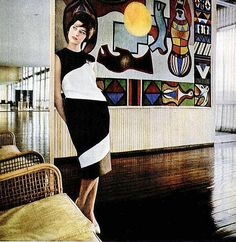 Marisa Woodward is wearing boldly striped dress by B.H.Wragge, photo by Howell Conant in front of tapestry by Brazilian artist Emiliano di Cavalcanti, 1960