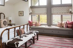 Country cabin girl's room features vaulted ceiling and long gray built-in window seat accented with pink and red pillows and windows dressed in white and gray quatrefoil roman shades. Rustic girl's bedroom with iron bed dressed in crisp white bedding and white and brown cowhide bench at foot of bed on red and brown striped rug layered over wood floors.