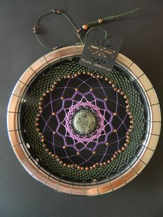 "Mandala tejido en aro cromado - 22 cm diameter (8 ½ "") - Chrome rim (bike) - Waxed thread (macramé) Green, Purple, light purple and grey - Applications of copper-colored metal and purple glass. - Center stone of Granite - 360 gr of weight. (Approximate)."