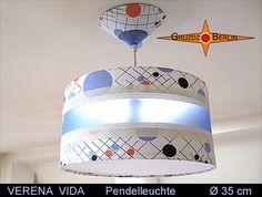 Leuchte VERENA VIDA Ø 35 cm Baldachin & Diffusor. Eine besondere Faszination geht von dieser Leuchte aus. Strahlend tritt der blaue Streifen aus transluzentem Material hervor. Für VERENA VIDA wurden verschiedene Materialen in Einklang gebracht: Das lichtblaue Polypropylen in einem rechteckigen Ausschnitt umrahmt von dem weißen Gitternetzgewebe Batyline und origninalem Retrostoff der 70er Jahre erzeugt eine sachliche, ruhige Atmoshäre im Raum.