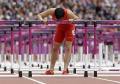China's Liu Xiang kisses his hurdle after falling in a men's 110-meter hurdles heat during the athletics in the Olympic Stadium.